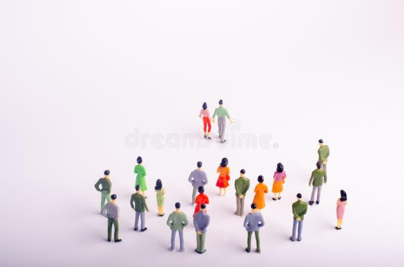 En folkmassa ser en man och en kvinna som går bort på en vit bakgrund En man och en kvinna lämnar folkmassan Par i lo arkivbilder