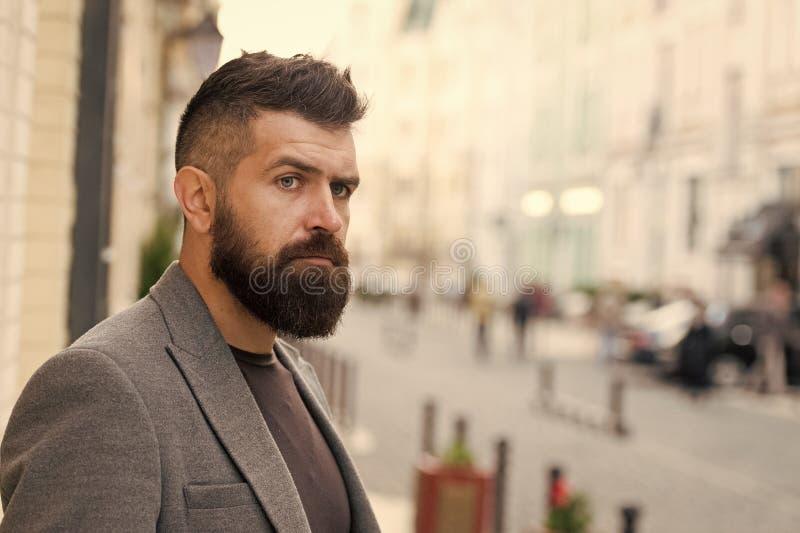 En fondo verde Hombre barbudo que va a trabajar Inconformista en estilo del negocio en la calle Hombre de negocios en ciudad mode imagen de archivo