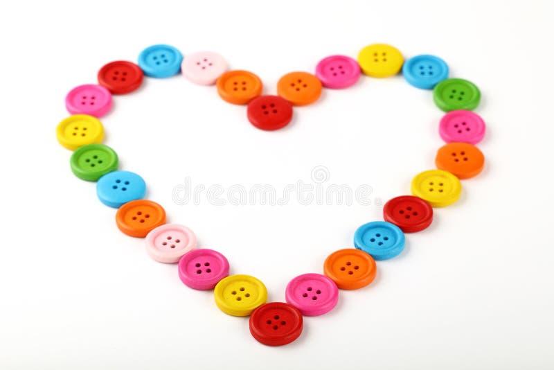 En forma de corazón de botones de costura coloridos en blanco foto de archivo libre de regalías