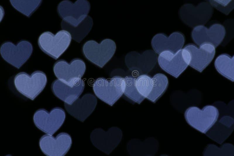 En forma de corazón colorido en el bokeh negro de la iluminación del fondo para la decoración en el papel pintado del contexto de foto de archivo libre de regalías