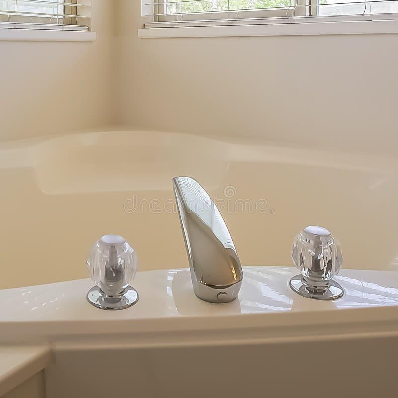 En forme de coeur brillant de cadre carré construit dans la baignoire au coin d'une salle de bains image stock