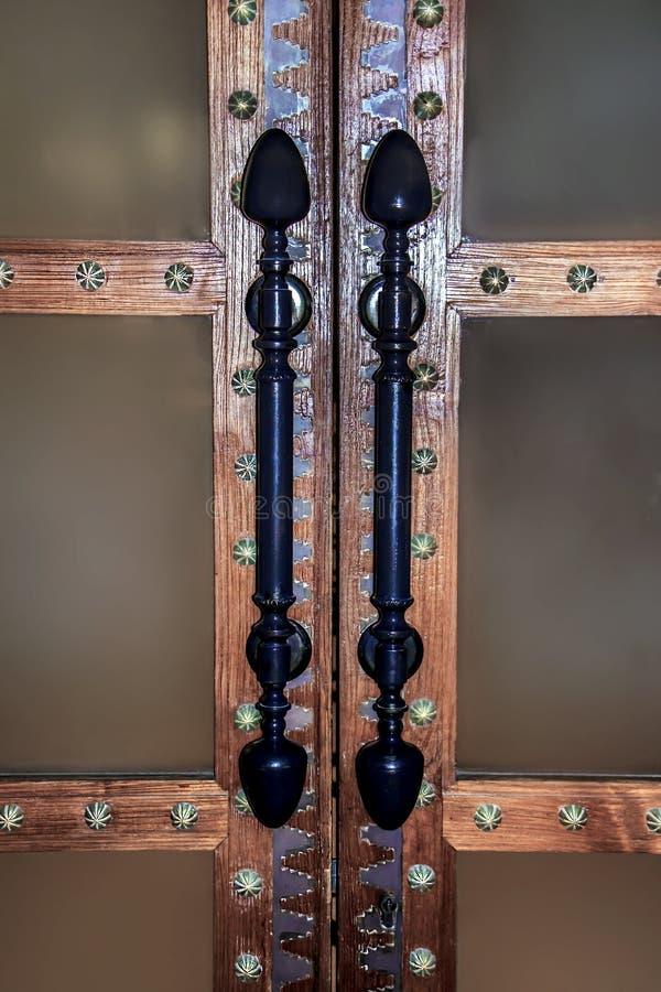 En forntida massiv dörr med en träorientering och nitar i en orientalisk stil Långa dubbletthandtag som göras av järn- metall, in royaltyfri fotografi