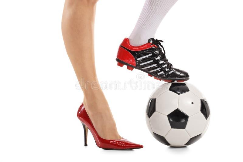 En fot i hög-heeled sko och annan i fotbollsko arkivfoto
