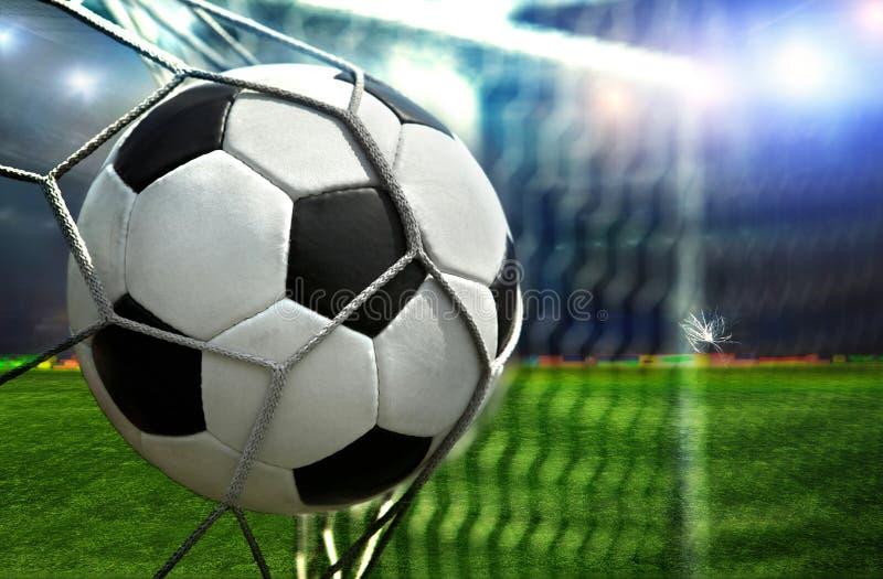 En fotbollboll gör poäng in i motståndaren arkivbilder