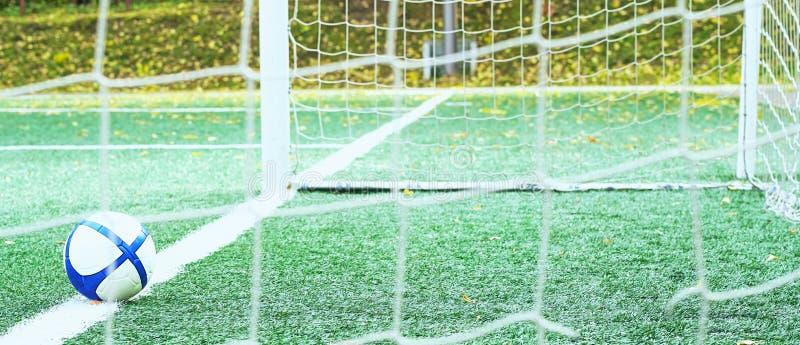 En fotbollboll ligger nära den vita mållinjen teckning på ett grönt fotbollfält Basket med belägger med metall påskyndar royaltyfri foto
