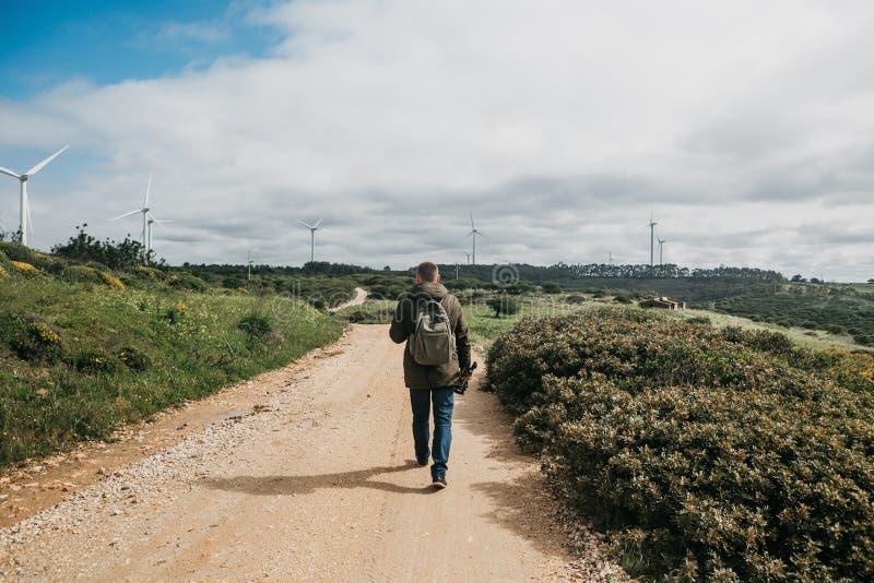 En fotograf eller en videographer eller en handelsresande med en ryggsäck och en tripod i hans hand går på vägen arkivbilder