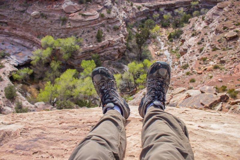 En fotvandrare dinglar hans fot över kanten av en klippa som ser ner in i en ökenkanjon royaltyfri bild