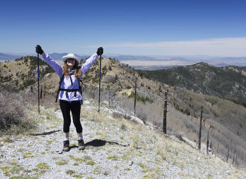 En fotvandrare firar nå toppmötet av ett berg arkivbilder