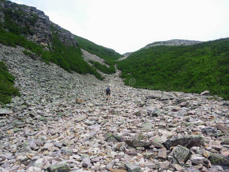 En fotvandrare som klättrar en massiv stenraslutning på vägen till toppmötet fotografering för bildbyråer