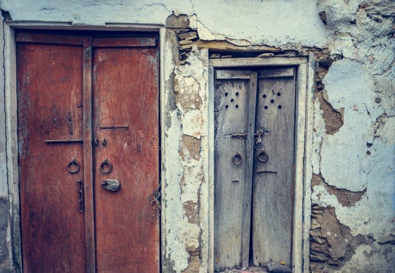 En främre sikt av gammalt tappningträ sned stängda dörrar av ett gammalt hus med den spruckna väggen i gator av den Lohara byn i  royaltyfri bild