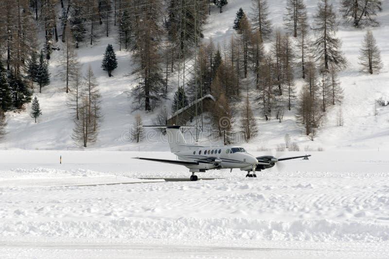 En främre sikt av en privat stråle som var klar att ta av i snön, täckte landskap och berg i fjällängarna Schweiz i vinter arkivbilder