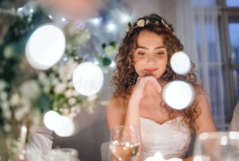 En främre sikt av en ung brud som sitter på en tabell på ett bröllop royaltyfri fotografi