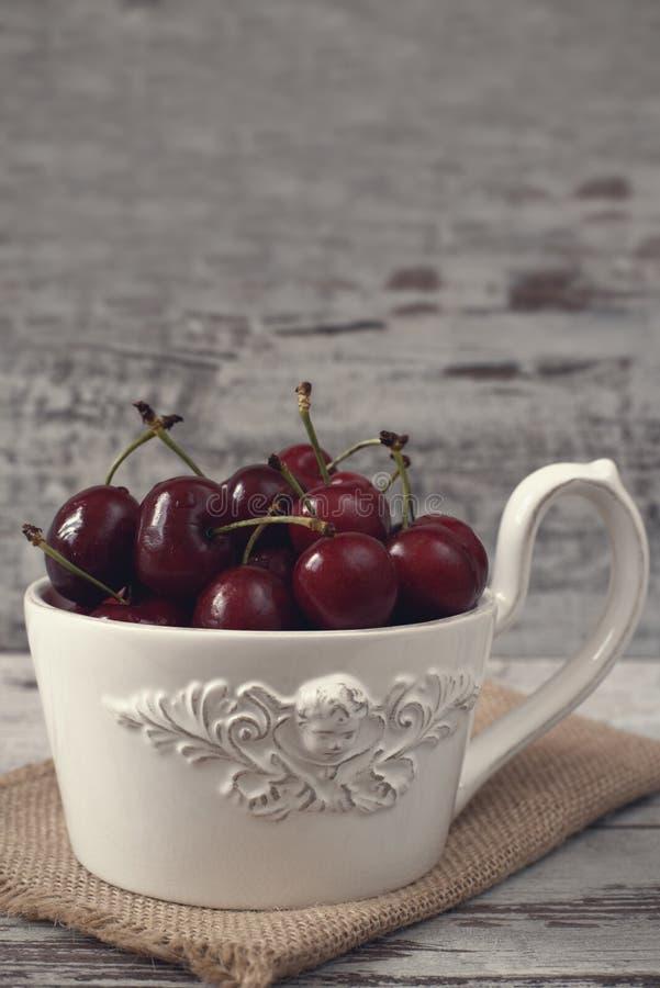 En främst ängel för stor kopp kaffe, vit bunke mycket med nya körsbär, frukter Ljus lantlig bakgrund, sjaskig stil, tappning t arkivbilder