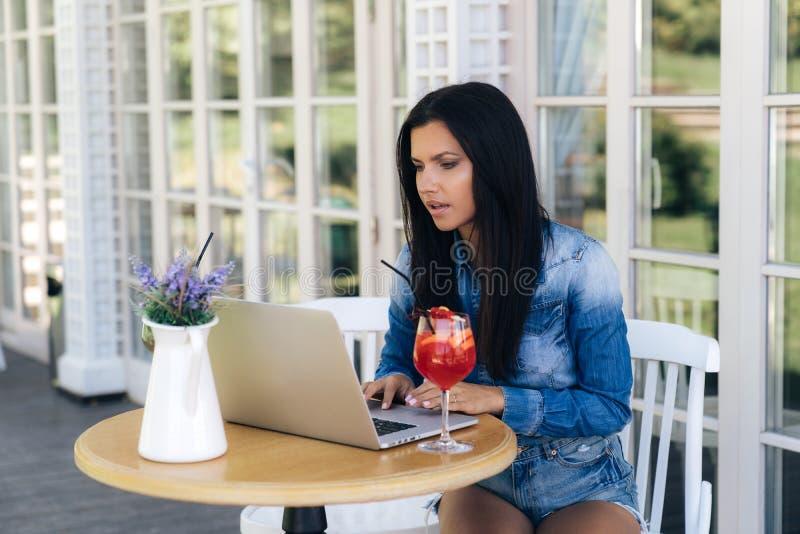 En freelancer för ung kvinna för affär sitter på en tabell i ett kafé, arbetar för en bärbar dator, koncentrerar på en bildskärm, fotografering för bildbyråer
