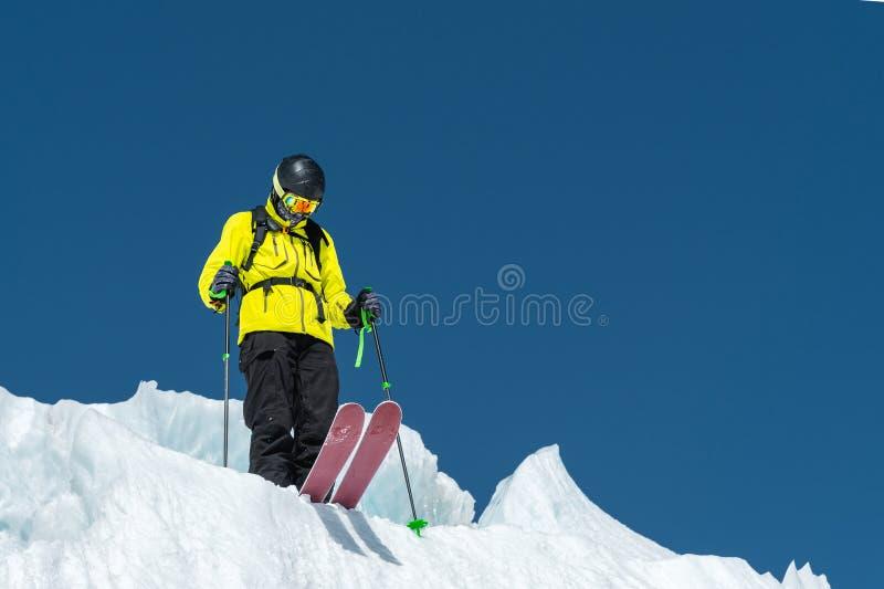 En freerider skidåkare i färdig dräkt står på en glaciär i det norr Kaukasuset Skidåkare som förbereder sig, innan att hoppa från arkivbilder