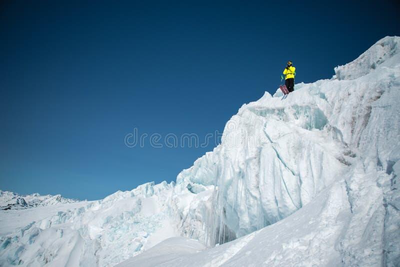 En freerider skidåkare i färdig dräkt står på en glaciär i det norr Kaukasuset Skidåkare som förbereder sig, innan att hoppa från royaltyfri bild