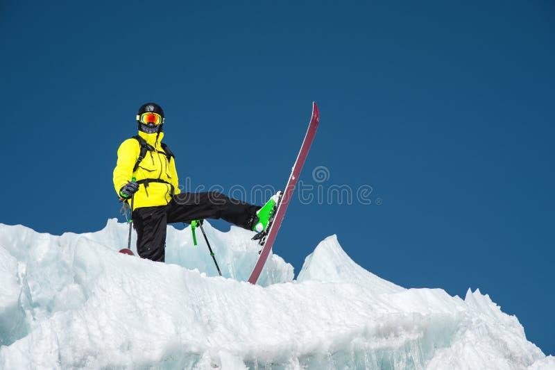En freerider skidåkare i färdig dräkt står på en glaciär i det norr Kaukasuset Skidåkare som förbereder sig, innan att hoppa från royaltyfri fotografi