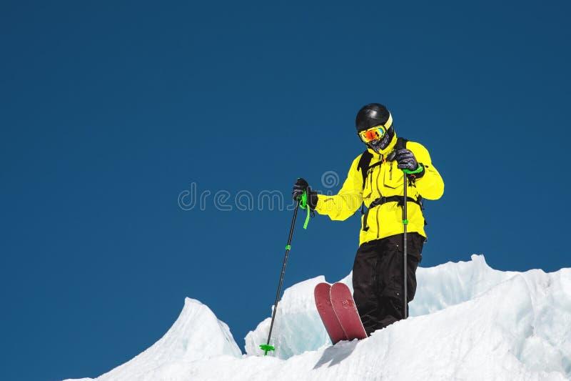 En freerider skidåkare i färdig dräkt står på en glaciär i det norr Kaukasuset Skidåkare som förbereder sig, innan att hoppa från arkivfoton