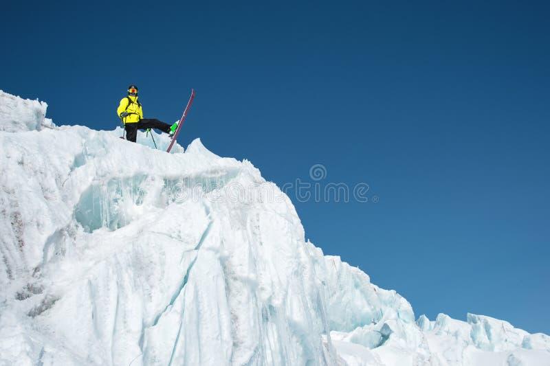 En freerider skidåkare i färdig dräkt står på en glaciär i det norr Kaukasuset Skidåkare som förbereder sig, innan att hoppa från arkivfoto