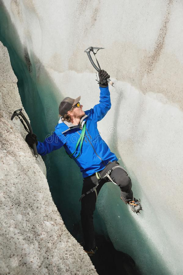 En fri klättrare utan försäkring med två isyxor stiger från en spricka i glaciären Fri klättring utan rep arkivbilder