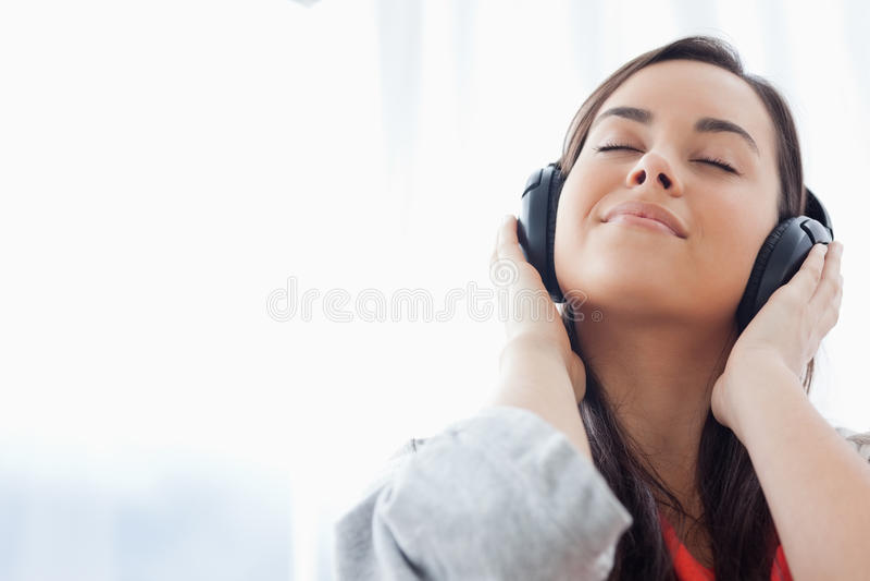 En fridsam kvinna som lyssnar till musik på henne hörlurar royaltyfri fotografi