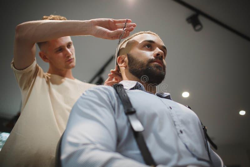 En frisördanandefrisyr för en man på en frisersalongbakgrund Ledar- bitande hår av mannen i en friseringsalong arkivbilder