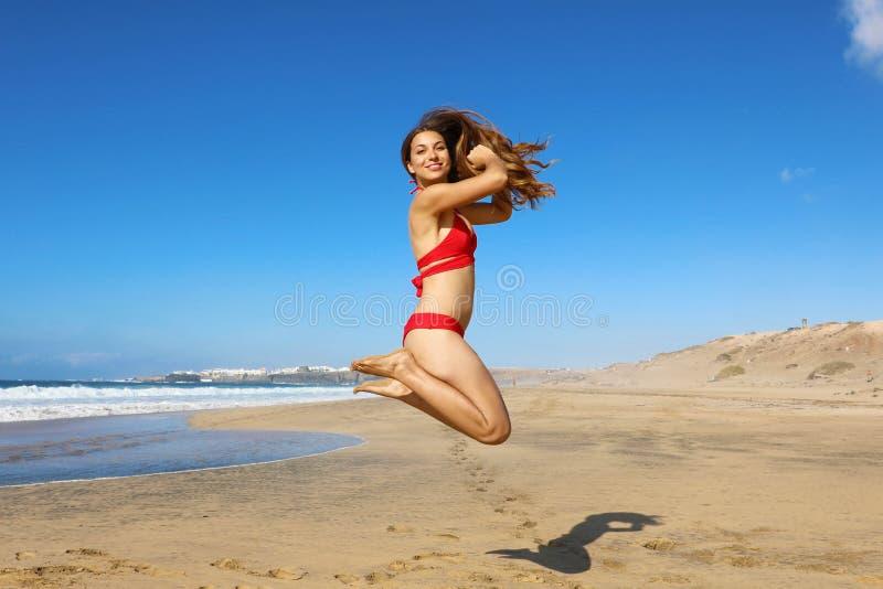 En frisk bikinisk kvinna som hoppar på stranden Glad leende flicka som gör ett hopp av frihet och lycka i en fri kropp på arkivbilder