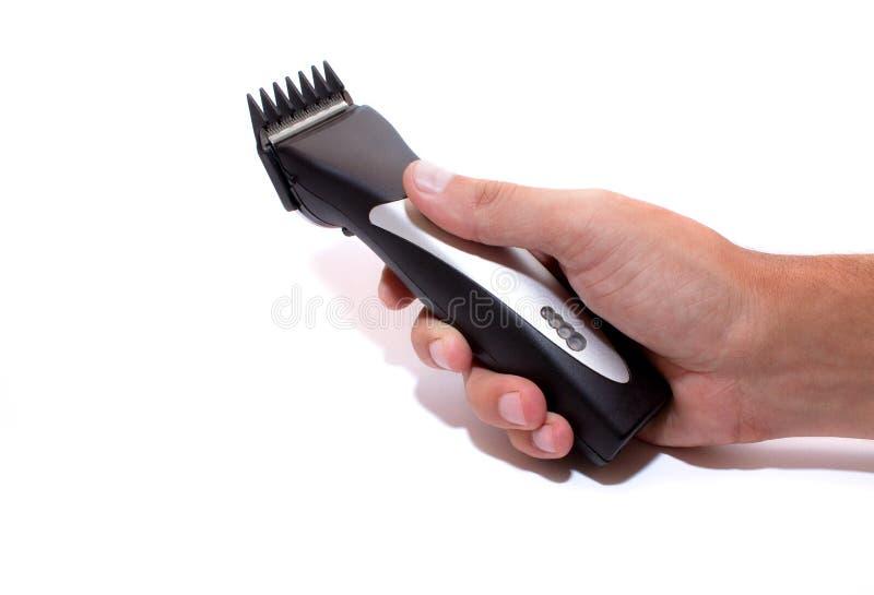 En frisyrmaskin _ Hårclipper i handen som isoleras på vit bakgrund royaltyfri fotografi
