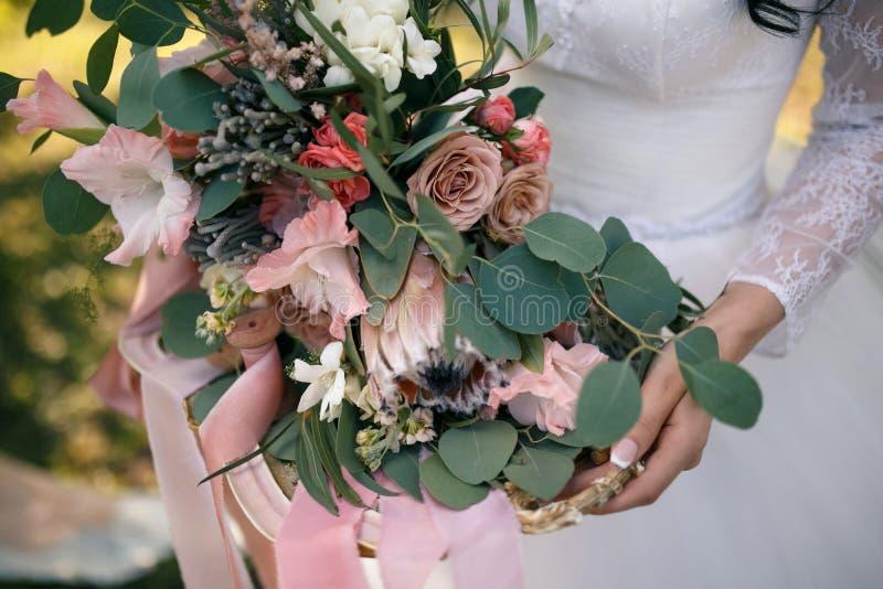 En frodig bröllopbukett av exotiska blommor på ett guld- magasin dekorerade med rosa band i händerna av bruden royaltyfri foto
