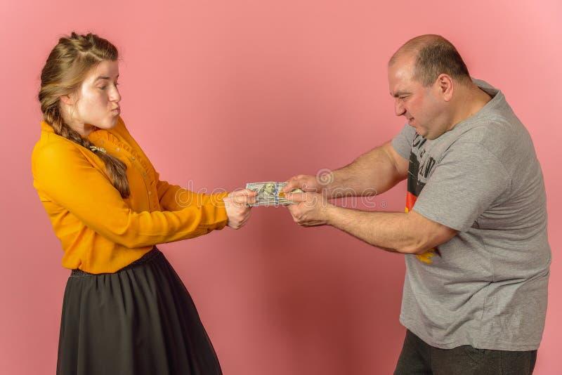 En fru tar pengar från sin man och vill få en gåva Greed in the social sphere Brist på medel för familjekonflikter arkivfoton