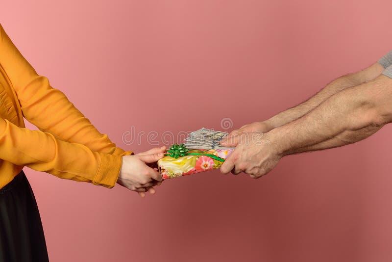 En fru tar pengar från sin man och vill få en gåva Greed in the social sphere Brist på medel för familjekonflikter arkivbild