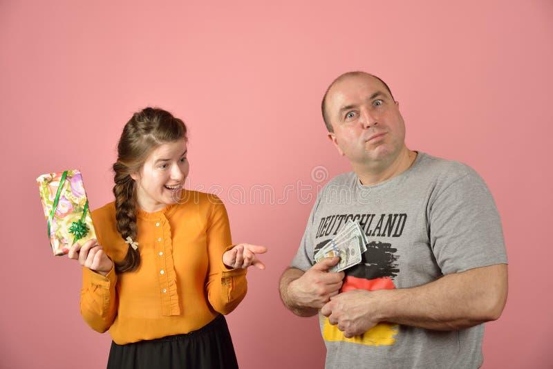 En fru tar pengar från sin man och vill få en gåva Greed in the social sphere Brist på medel för familjekonflikter royaltyfri fotografi