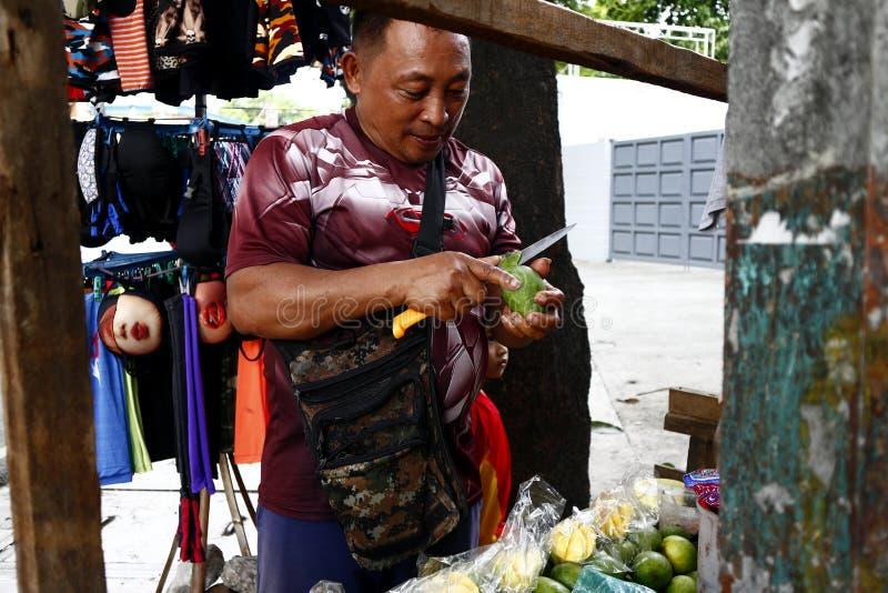En fruktförsäljare skalar och skivar en indisk mango som han säljer på hans fruktvagn arkivfoton