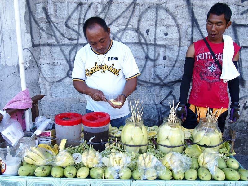 En fruktförsäljare som skivar en grön mango, medan en kund ser på royaltyfria foton