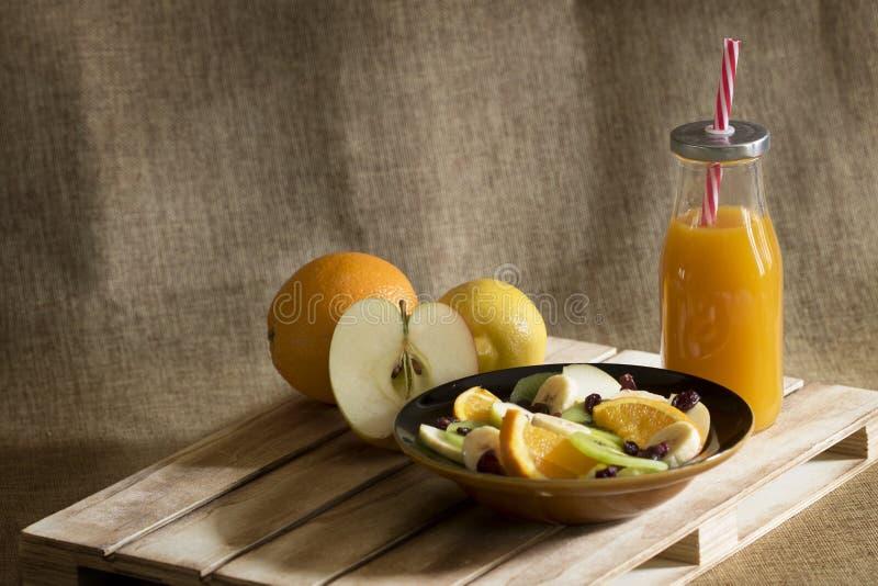 En fruktsallad, en flaska av mangofruktsaft och några stycken av ny frukt royaltyfria bilder