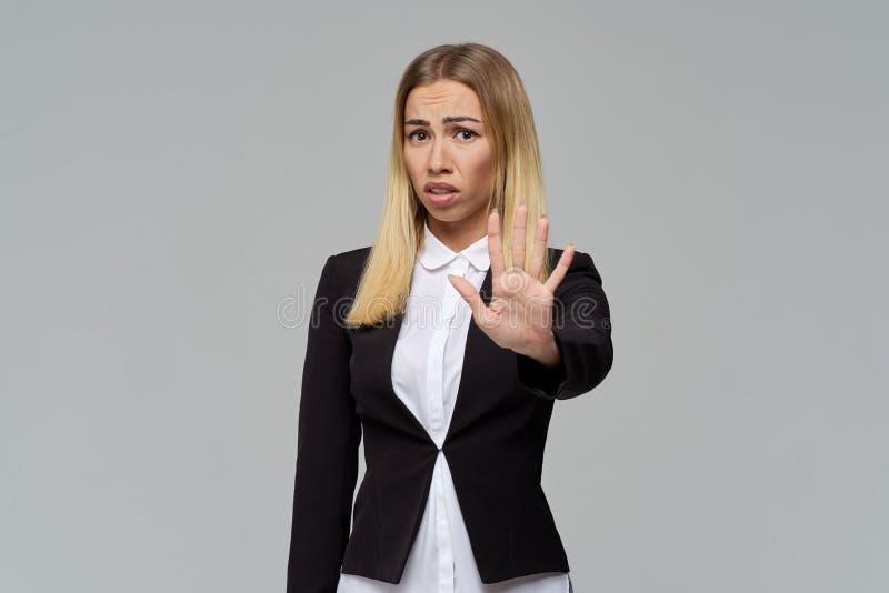 En frustrerad ung affärskvinna rynkar pannan hennes ögonbryn och visar ett tecken av vägranen med hennes hand, frågar att stoppa royaltyfri fotografi