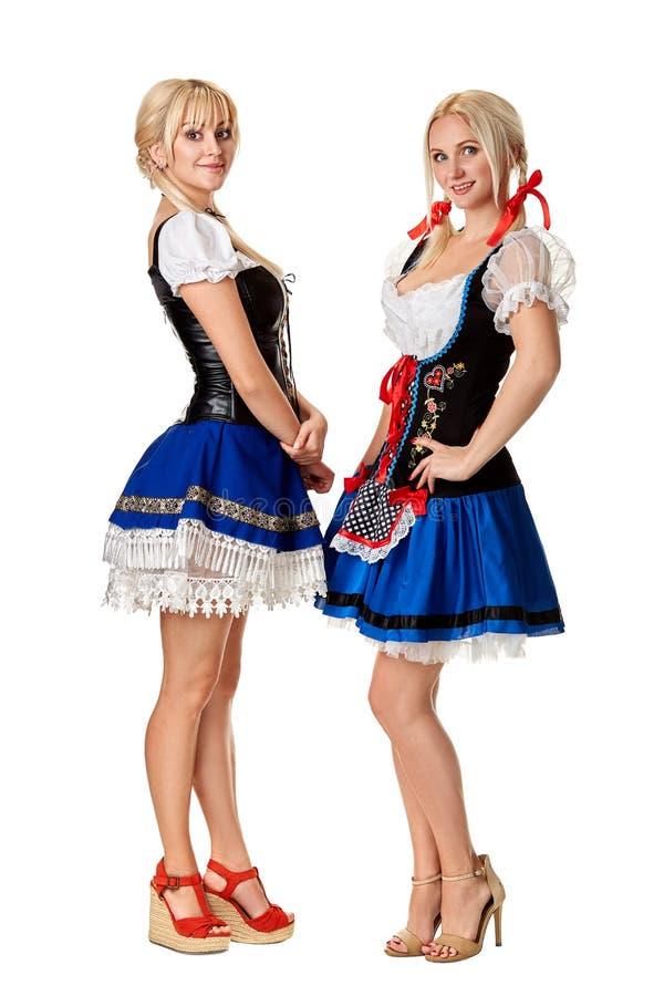 En full längdstående av två härliga kvinnor i en traditionell dräkt som isoleras på vit oktoberfest royaltyfri foto