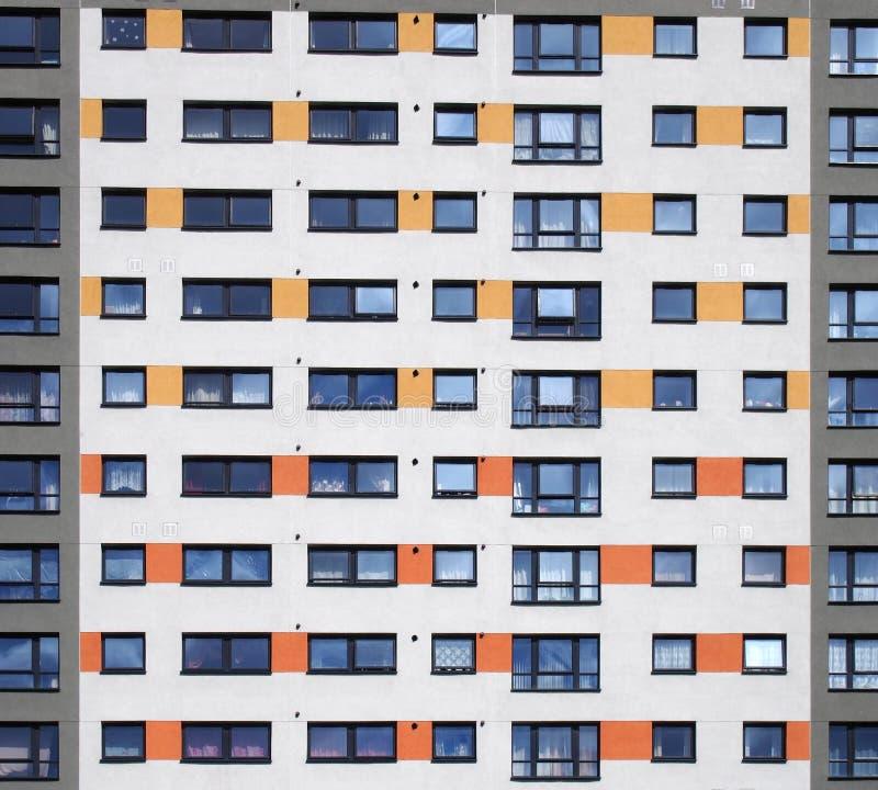 en full rambild av fönster i en stor hög löneförhöjninghyreshus med att upprepa rader av fönster med vita väggar med apelsinen fotografering för bildbyråer