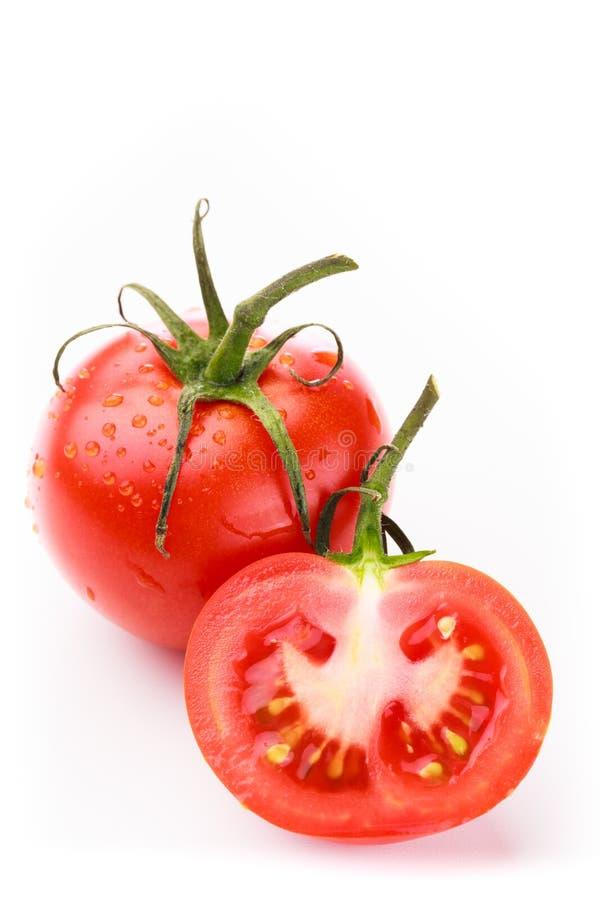 En full tomat och halvan tomat arkivbild