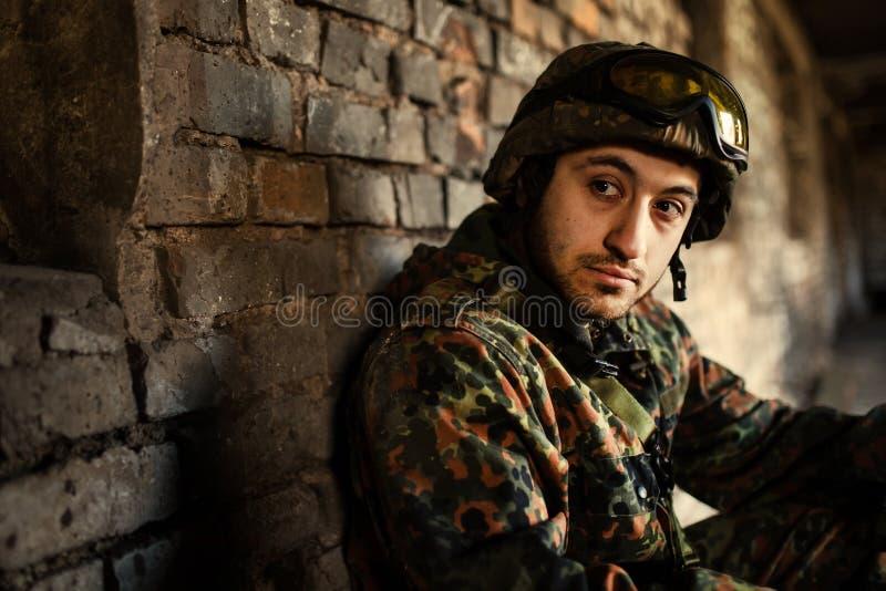 En fundersam soldat som vilar från en militär operation royaltyfri bild
