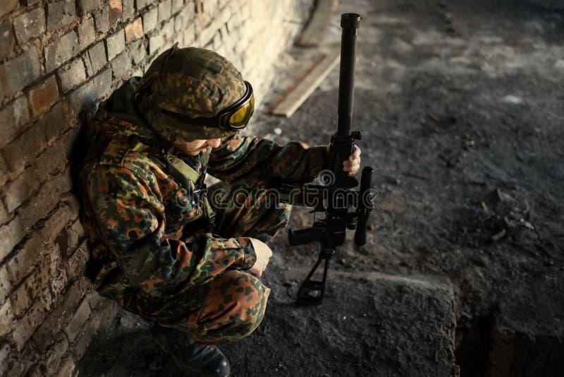En fundersam soldat som vilar från en militär operation arkivfoton