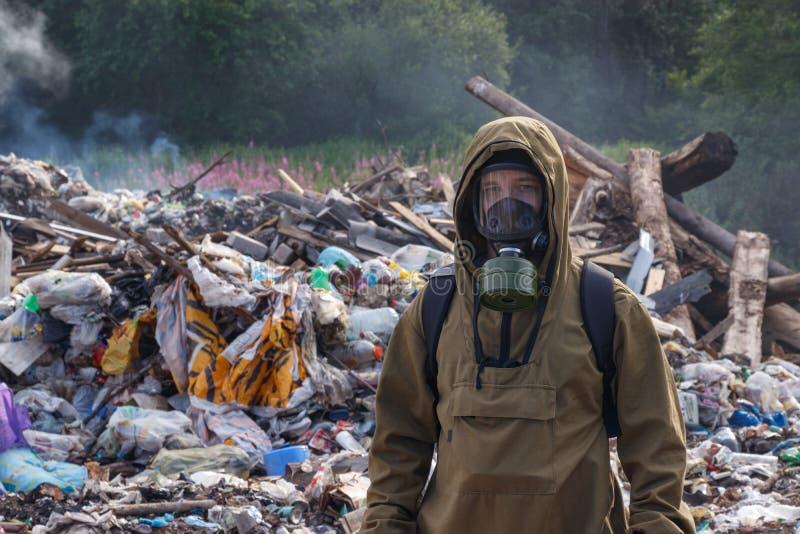 En funktionsduglig man i en gasmask mot bakgrunden av brinnande avskräde Många plastpåsar som kastas till förrådsplatsen Från pla royaltyfri fotografi