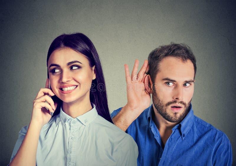En fuskflickvän Nyfiken man som lyssnar i hemlighet till en lycklig kvinna som talar på mobiltelefonen med hennes vän arkivfoto