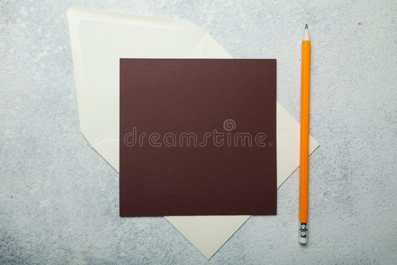 En fyrkantig brun bokstav på en vit tappningbakgrund royaltyfri foto