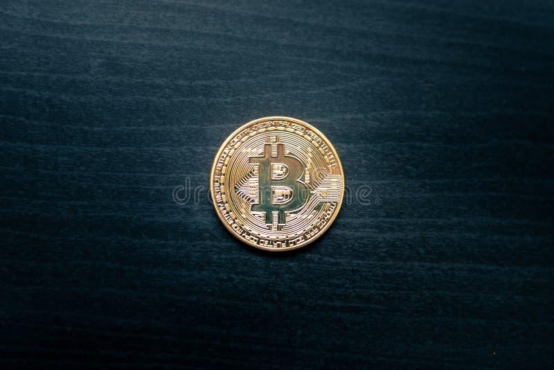 En fysisk bitcoin i mitt av en mörk träbakgrund arkivbilder
