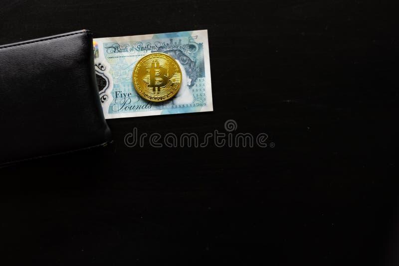 En fysisk bitcoin sitter överst av engelska pund bredvid en plånbok royaltyfri bild