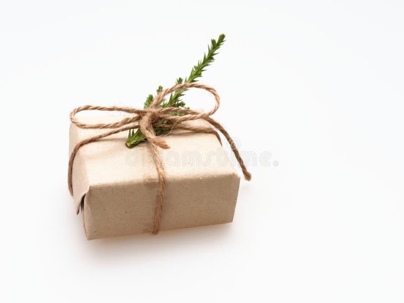 En gåva- eller gåvaask som sloggs in av busebrunt, återanvände papper, och bundet med det bruna hamparepbandet med sörja filialen royaltyfri fotografi