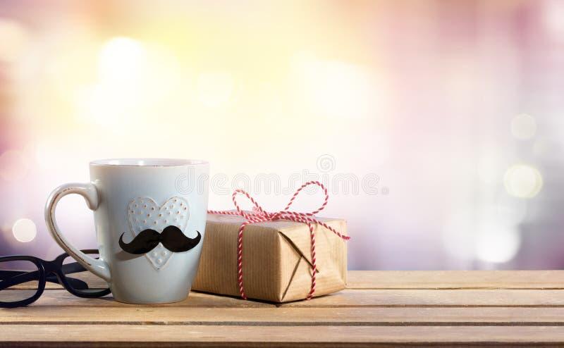 En gåva för faderdagen - gåva med exponeringsglas och kaffekoppen arkivfoto