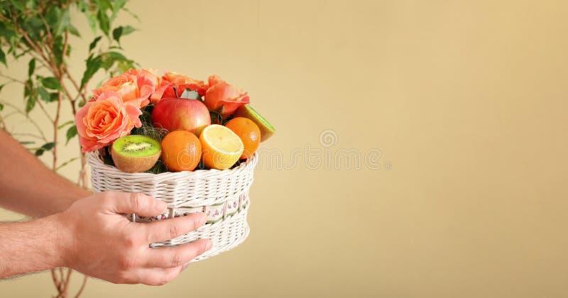 En gåva i form av en korg med blommor och frukter arkivbild
