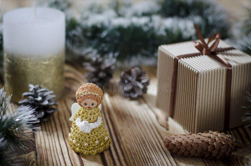 En gåva lägger på en trätabell bredvid en stearinljus, kottar och en ängel mot bakgrunden av julpynt arkivbild